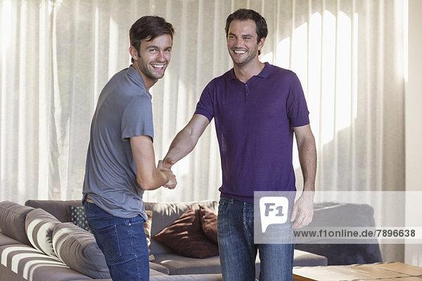 Zwei Freunde  die sich die Hände schütteln und lächeln.