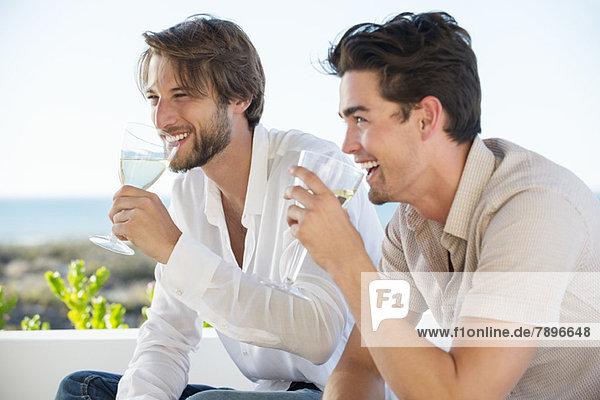 Zwei männliche Freunde genießen Weißwein im Freien