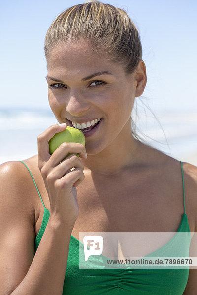 Porträt einer lächelnden Frau beim Essen eines grünen Apfels