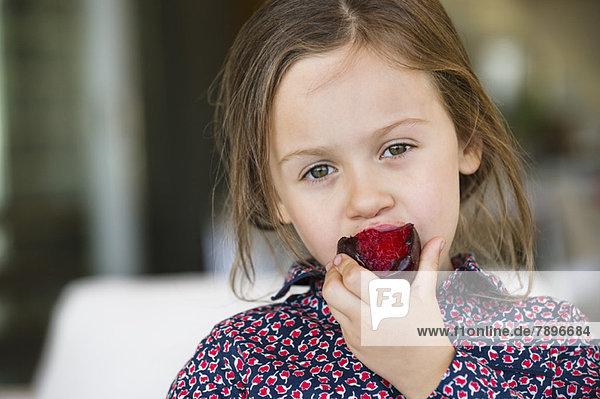 Porträt eines Mädchens beim Pflaumenessen