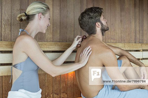 Frau massiert den Rücken ihrer Freundin mit einem Massagegerät in der Sauna.