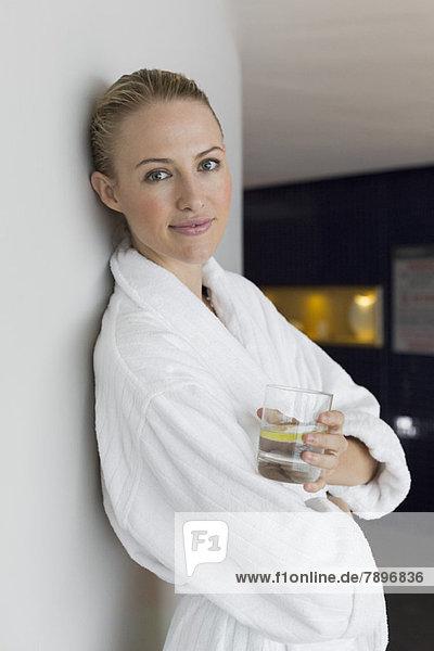 Frau im Bademantel trinkt Limonade im Spa