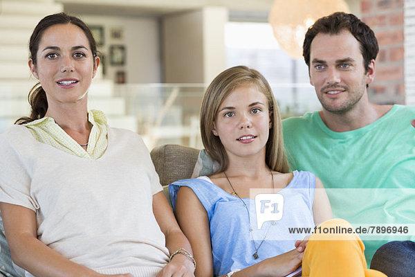 Porträt einer Familie auf einer Couch sitzend und lächelnd