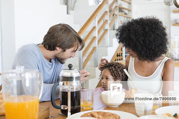 Eltern mit ihrer Tochter am Esstisch