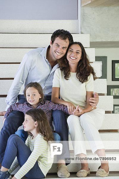 Paar mit ihren Kindern auf einer Treppe sitzend