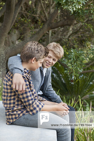 Two teenage boys sitting together and discussing