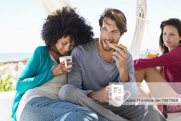 Pärchen beim Kaffee mit ihrem Freund im Hintergrund