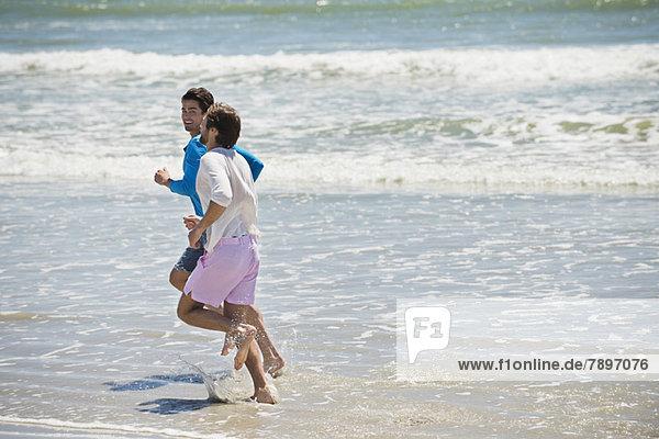 Zwei Männer  die am Strand rennen.