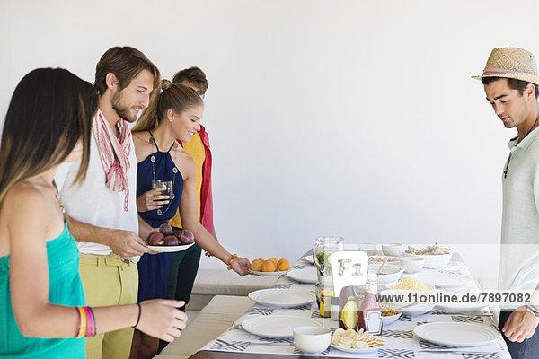 Freunde arrangieren Essen auf einem Esstisch