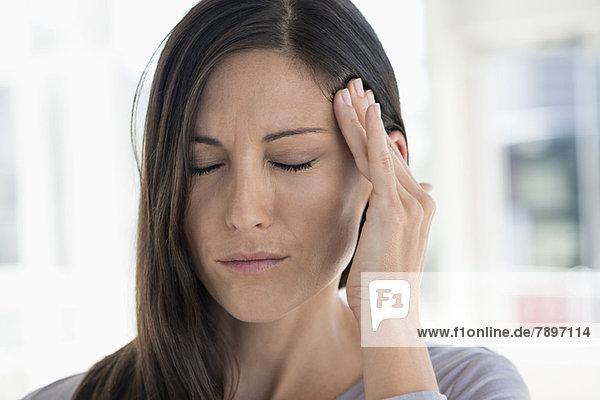 Nahaufnahme einer Frau mit Kopfschmerzen