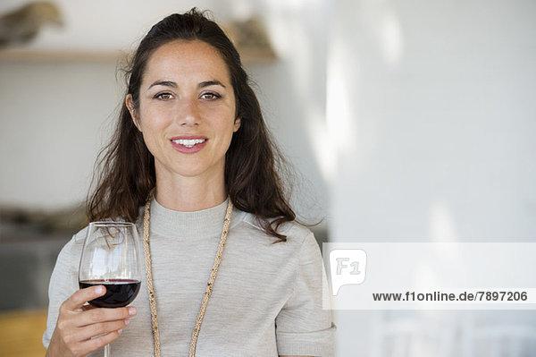 Porträt einer Frau  die ein Weinglas hält und lächelt