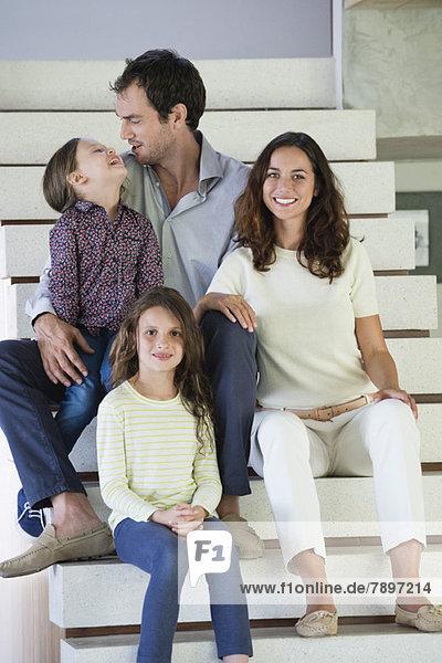 Familie sitzt auf der Treppe und lächelt