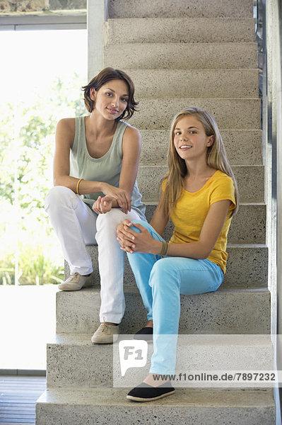 Porträt einer Frau und ihrer Tochter auf einer Treppe sitzend