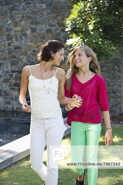 Lächelnde Mutter und Tochter gehen und halten sich gegenseitig die Hände.