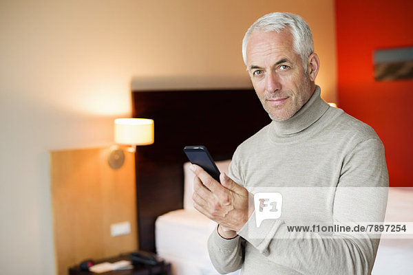 Man using a cell phone in a hotel room