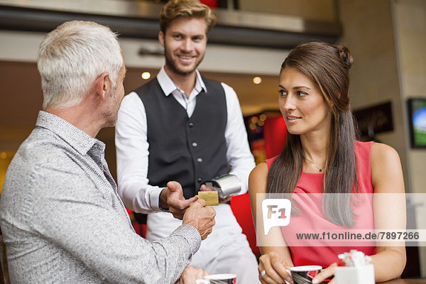 Couple paying with a credit card to a waiter in a restaurant