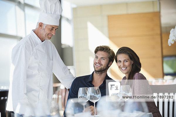 Chefkoch im Gespräch mit einem Paar im Restaurant Chefkoch im Gespräch mit einem Paar im Restaurant