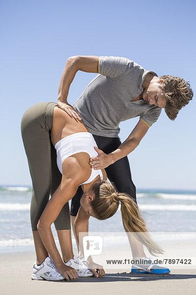 Mann hilft Frau beim Strecken am Strand