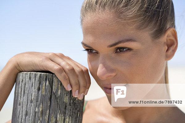 Nahaufnahme einer Frau in der Nähe eines Holzpfostens