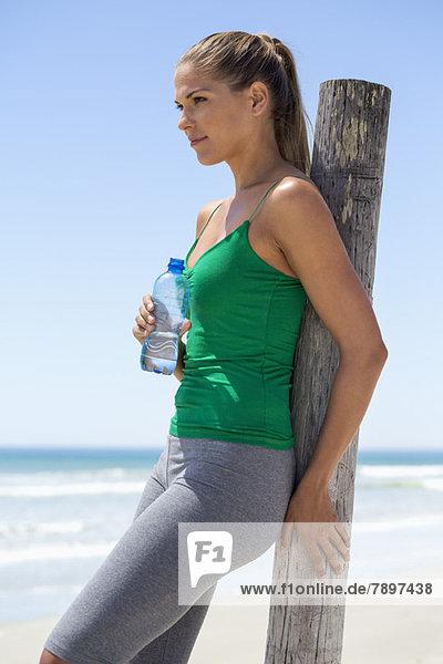 Frau lehnt sich an einen Holzpfosten am Strand und hält eine Wasserflasche.