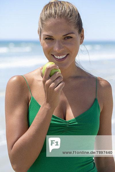Lächelnde Frau beim Essen eines grünen Apfels