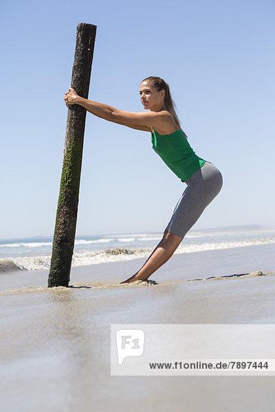 Frau beim Training mit einem Holzpfosten am Strand