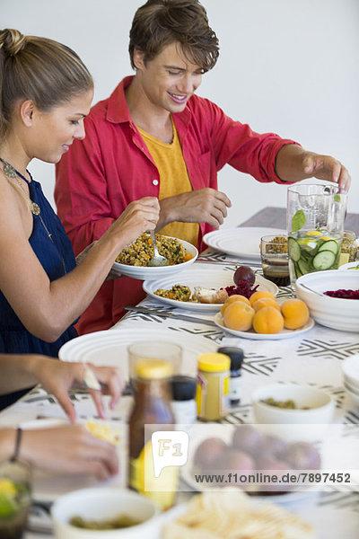 Freunde am Esstisch beim Mittagessen