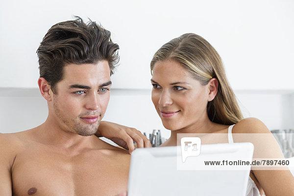 Paar Lesung eines digitalen Tabletts im Bett
