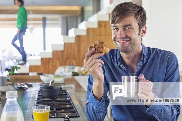 Mann beim Frühstück an der Küchenzeile mit seiner Frau im Hintergrund