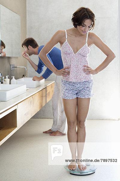 Frau misst ihr Gewicht auf einer Waage mit ihrem Mann im Hintergrund