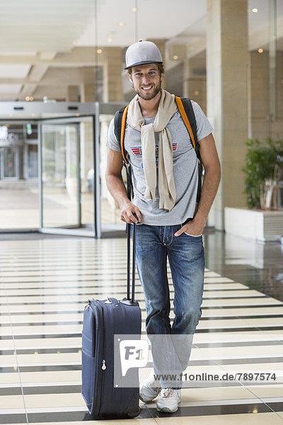 Mann steht mit seinem Gepäck am Flughafen