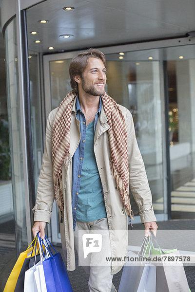 Mann trägt Einkaufstaschen und lächelt
