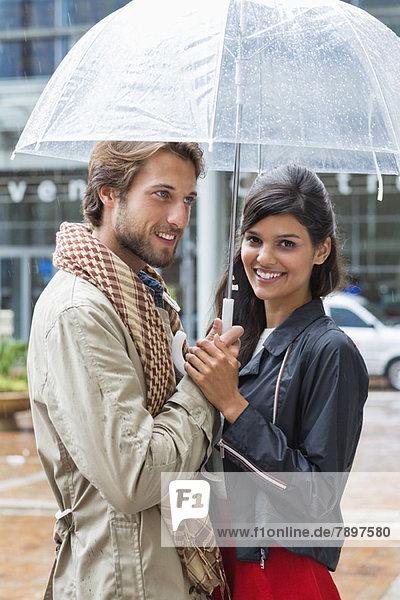 Lächelndes Paar unter einem Schirm