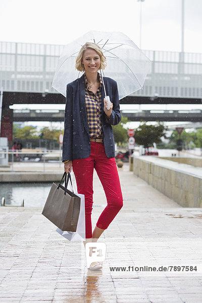 Lächelnde Frau unter einem Regenschirm mit Einkaufstaschen