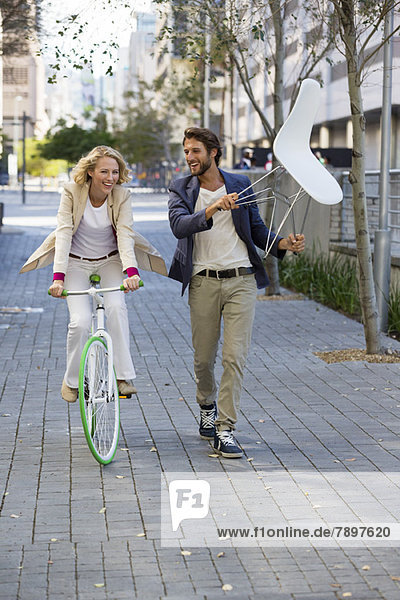 Woman riding a bicycle with a man carrying a chair beside her