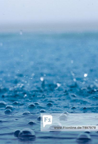 Regentropfen fallen ins Meer