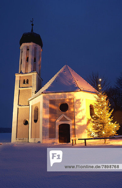 Illuminated chapel at dusk in winter with a Christmas tree