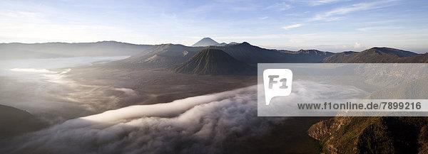Morgennebel in der Tengger-Caldera mit dem Vulkan Bromo  Krater Mitte links  Vulkan Batok  Mitte  hinten Vulkan Semeru