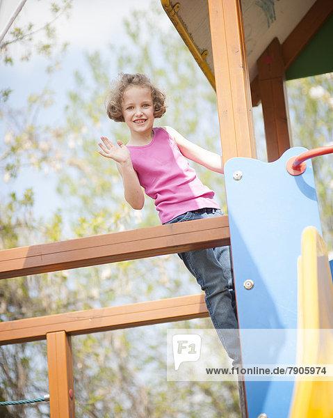 winken  Spielplatz  Blick in die Kamera  jung  Kind  Mädchen  klettern