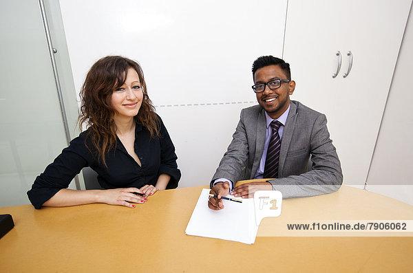 arbeiten  Kollege  multikulturell  Tisch  Schreibarbeit  unterschreiben