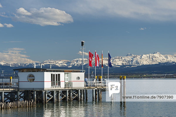 Germany  Ferry jetty with flags and snow covered Swiss Alps at Lake Constance