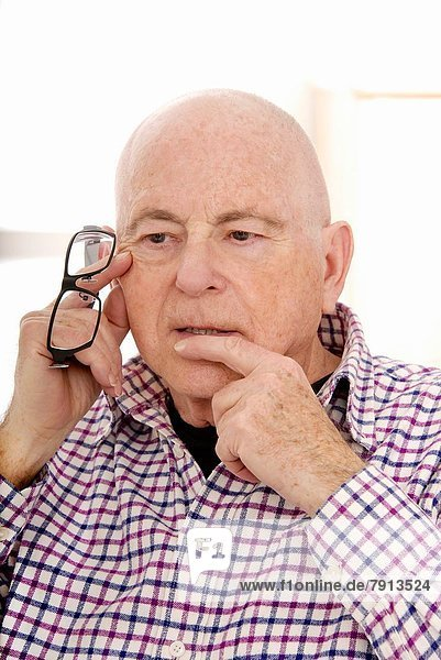 Senior Man head in chin holding spectacles  in a thoughtful puzzled mood