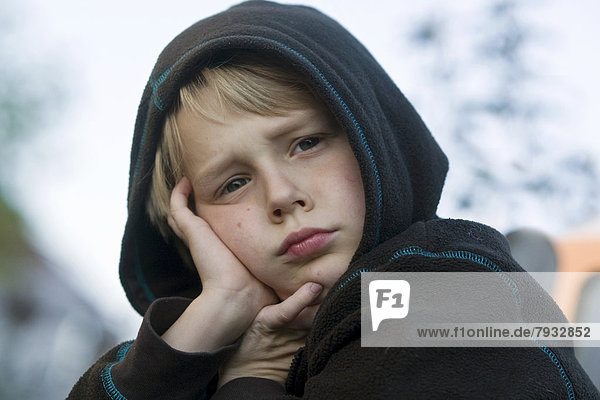 Boy  8  wearing a hood and looking bored