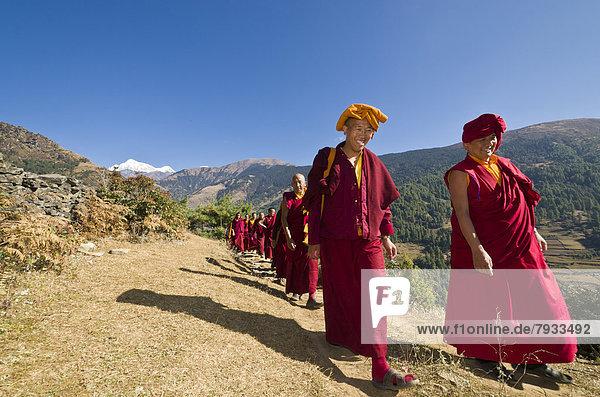 Mönche und Nonnen in roten Gewändern  zu Fuss auf einem Pfad an einem Berghang