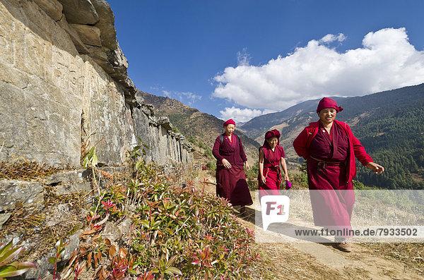 Mönche und Nonnen in roten Gewändern zu Fuß unterwegs auf einem Pfad an einem Berghang