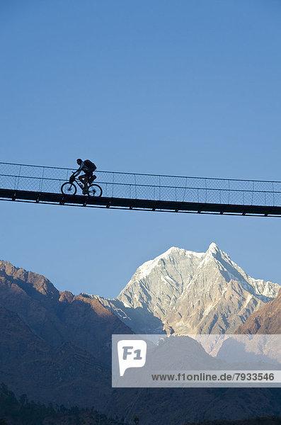 Ein Radfahrer überquert eine Hängebrücke über der Kali Gandaki Schlucht  Nilgiris oder Nilgiri-Berge hinten