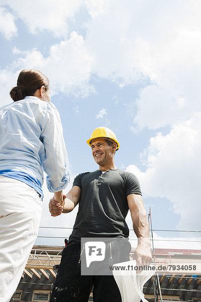 Bauleiter und Bauherrin begrüßen sich auf der Baustelle