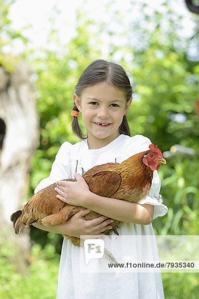 Mädchen hält ein Huhn