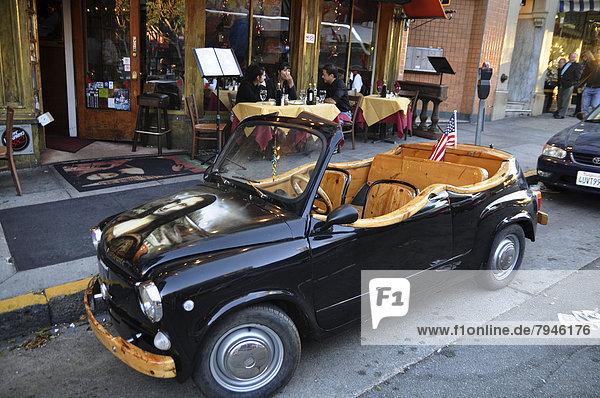 Mona Lisa Mini  Oldtimer  vor einem Straßencafé geparkt