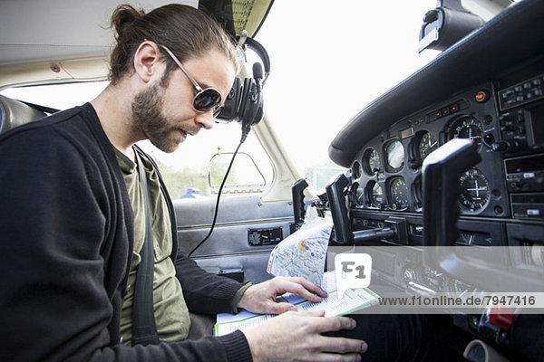 Seitenansicht des Mittelpiloten mit Klemmbrett im Cockpit des Privatflugzeugs